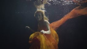 Mysterious woman swimming like mermaid under water in on dark background. Fashion woman underwater in swimming pool posing and looking into camera stock video footage