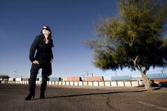 Mysterious Woman in a Trenchcoat. Mysterious woman in black trenchcoat and sunglasses at train yard Royalty Free Stock Photo