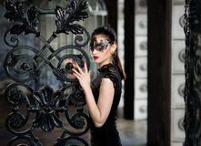 Mysterious woman in venetian carnival mask near wrought iron gate Stock Photo