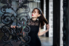 Mysterious woman in venetian carnival mask near wrought iron gate Stock Images