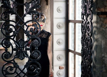 Mysterious woman in venetian carnival mask near wrought iron gate Royalty Free Stock Image