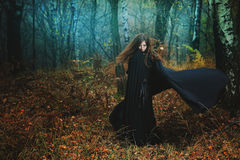 Mysterious woman walking in magical forest royalty free stock photos