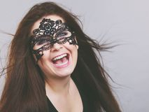 Mysterious woman wearing lace mask. Happy pretty mysterious woman wearing black eye lace mask having tousled windblown long brown hair stock photo