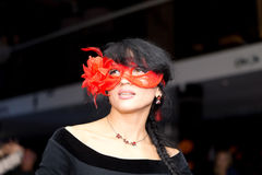 Mysterious woman wearing masquerade eye mask. Portrait of a mysterious beautiful brunette Hispanic woman wearing a red Venetian masquerade eye mask, in a hall royalty free stock photos