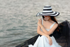 Mysterious  Woman in White Dress Sitting in an Old Boat Stock Photography