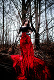 Mysterious woman or witch in long red dress standing in dark forest Stock Image