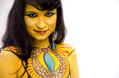 Mysterious yellow bodypainted tribal face of a girl on a white background. royalty free stock photos