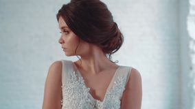 Mysterious young attractive brunette girl in a long, luxurious, white-faced dress stands in the studio, looks away