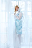 Mysterious young blond woman looking through transparent curtains Stock Photos