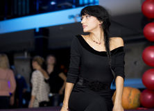 Mysterious young brunette woman waiting in a hall. Mysterious attractive young brunette woman wearing a elegant black dress, waiting in a crowded hall royalty free stock photos