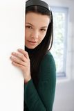 Mysterious young female hiding behind wall. Young attractive female hiding behind wall, leaning to it, looking at camera Royalty Free Stock Images