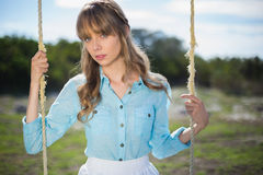 Mysterious young model relaxing sitting on swing Royalty Free Stock Photo