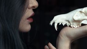 Mysterious young witch whispers a curse and spell holding a skull in the hands of a fox. Painted long hair jewelry rings on the fingers. Close-up. Halloween stock footage