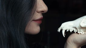 Mysterious young witch whispers a curse and spell holding a skull in the hands of a fox. Painted long hair jewelry rings on the fingers. Close-up. Halloween stock video footage