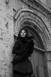Mysterious young woman in black coat and fur. Standing next to the old building Royalty Free Stock Photos