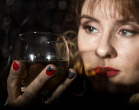 Mysterious young woman with a glass of wine posing behind transparent glass covered by water drops. on a dark background Royalty Free Stock Photography