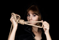 Mysterious young woman holding loop of the rope. on a dark background.  Royalty Free Stock Photography