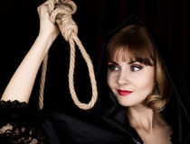 Mysterious young woman holding loop of the rope. on a dark background.  Royalty Free Stock Images