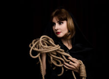 Mysterious young woman holding loop of the rope. on a dark background.  Stock Photos