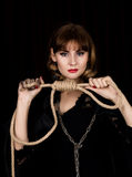 Mysterious young woman holding loop of the rope. on a dark background.  Royalty Free Stock Image
