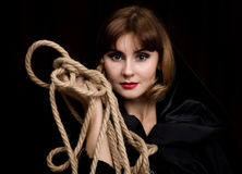 Mysterious young woman holding loop of the rope. on a dark background.  Royalty Free Stock Photo