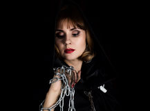 Mysterious young woman holding rope and chain. on a dark background Royalty Free Stock Photography