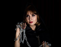 Mysterious young woman holding rope and chain. on a dark background Stock Images