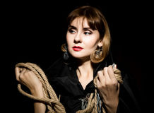 Mysterious young woman holding rope. on a dark background Stock Image