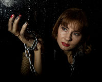 Mysterious young woman holding rope. on a dark background Royalty Free Stock Images