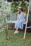 Mysterious Young Woman In A Hat Sits On A Swing Royalty Free Stock Photos