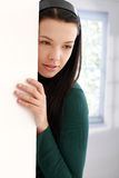 Mysterious young woman leaning to wall thinking Stock Photos