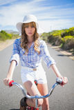 Mysterious young woman posing while riding bike Stock Photo