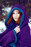 Mysterious young woman in purple cape with a hood Royalty Free Stock Image