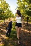 Mysterious young woman is walking by path in green orchard, she looks in other side with flowing hair, keeps black jacket in hand. Mysterious young woman is stock photos