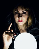 Mysterious young woman wonders on a large luminous ball. on a dark background Royalty Free Stock Photography