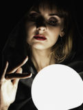 Mysterious young woman wonders on a large luminous ball. on a dark background Stock Photo