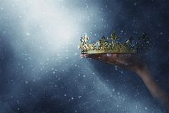 Mysteriousand magical image of woman`s hand holding a gold crown over gothic black background. Medieval period concept. Mysteriousand magical image of woman`s stock images
