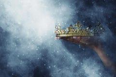 Mysteriousand magiczny wizerunek kobiety ` s ręka trzyma złocistą koronę nad gothic czarnym tłem średniowieczny okresu pojęcie obrazy royalty free