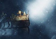 Mysteriousand magisch beeld van oud kroon en boek over gotische zwarte achtergrond middeleeuws periodeconcept stock foto's