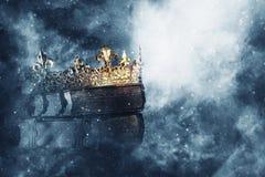 Mysteriousand magisch beeld van oud kroon en boek over gotische zwarte achtergrond middeleeuws periodeconcept royalty-vrije stock foto