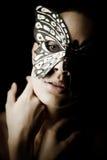 Mysteriöses schönes Mädchen in der Schmetterlingsmaske Lizenzfreies Stockfoto