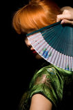 Mystery. Redhead girl in chinese dress playing with fan Stock Photo