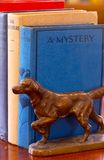 Mystery and Adventure Books. Old mystery and adventure books with hunting dog pointing as bookend royalty free stock images