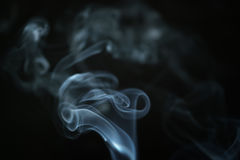 Mystery blue smoke over dark background closeup Stock Photos