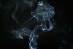 Mystery blue smoke over dark background closeup Royalty Free Stock Image
