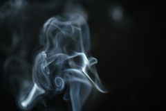 Mystery blue smoke over dark background closeup Royalty Free Stock Images