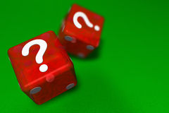 Mystery Dice. Two red casino dice landing question mark sided up on green cloth suggesting mystery with shallow depth of field and copy space Stock Photo