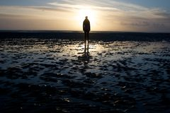 Mystery Figure. A mysterious figure stands alone on the beach Royalty Free Stock Photo