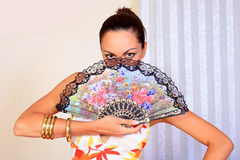 Mystery girl holding a fan Royalty Free Stock Photo