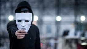 Mystery hoodie man with black mask holding white mask in his hand. Anonymous social masking or bipolar disorder concept. Focus on white mask stock photography